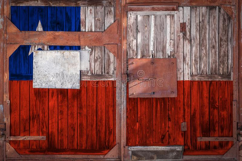 Close-up of old warehouse gate with national flag. Of Ð¡hile. The concept of export-import Chile, storage of goods and national delivery of goods. Flag in royalty free illustration