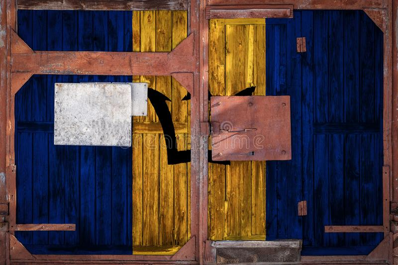 Close-up of old warehouse gate with national flag. Of Barbados. The concept of export-import Barbados, storage of goods and national delivery of goods. Flag in royalty free illustration