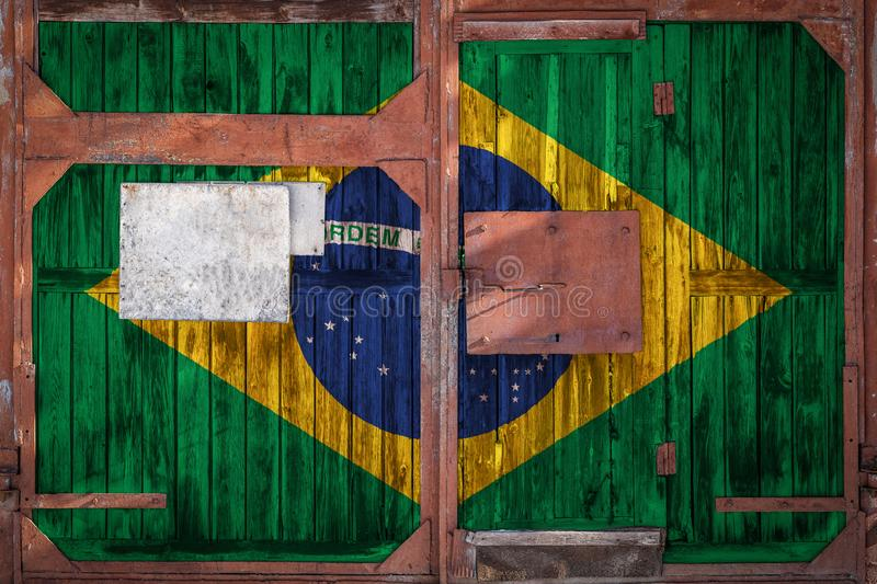 Close-up of old warehouse gate with national flag. Of Brazil. The concept of export-import Brazil, storage of goods and national delivery of goods. Flag in royalty free illustration
