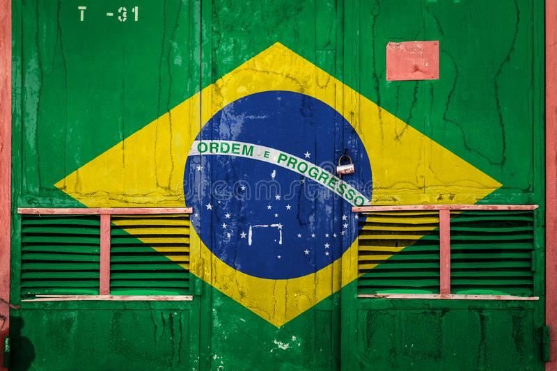 Close-up of old warehouse gate with national flag. Of Brazil. Concept of Brazil export-import, storage of goods and national delivery of goods. Flag in grunge stock illustration