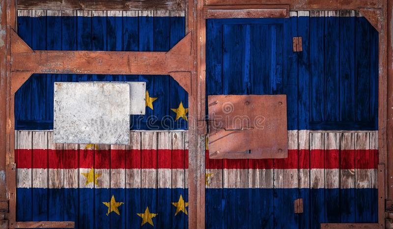 Close-up of old warehouse gate with national flag. Close-up of an old warehouse gate with the national flag of Cape Verde. The concept of export-import Cape royalty free illustration
