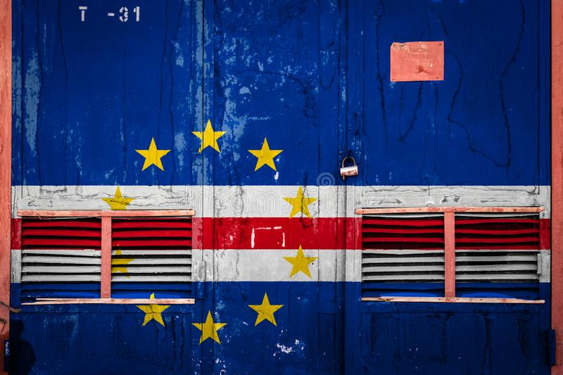 Close-up of old warehouse gate with national flag. Of Cape Verde. Concept of Cape Verde export-import, storage of goods and national delivery of goods. Flag in stock illustration