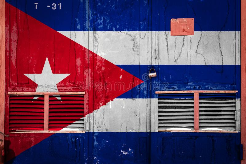 Close-up of old warehouse gate with national flag. Of Cuba. Concept of Cuba export-import, storage of goods and national delivery of goods. Flag in grunge style royalty free stock photography