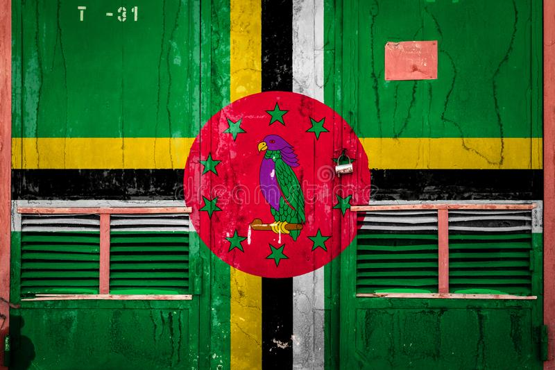 Close-up of old warehouse gate with national flag. Of Dominica. Concept of Dominica export-import, storage of goods and national delivery of goods. Flag in vector illustration