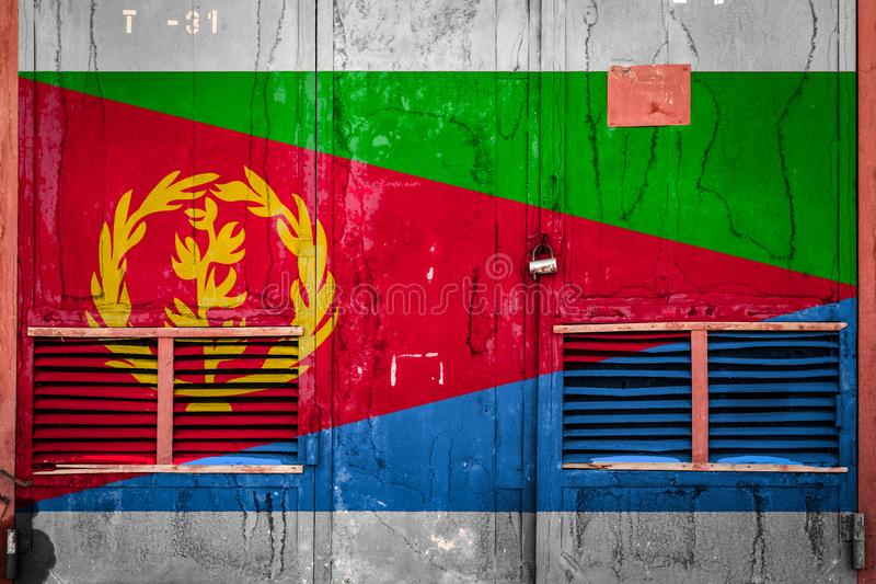 Close-up of old warehouse gate with national flag. Of Eitrea. Concept of Eritrea export-import, storage of goods and national delivery of goods. Flag in grunge stock illustration