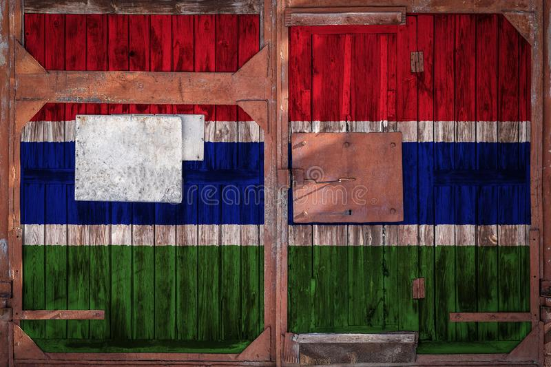 Close-up of old warehouse gate with national flag. Of the Gambia. The concept of export-import Gambia, storage of goods and national delivery of goods. Flag in vector illustration