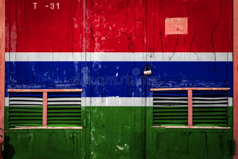Close-up of old warehouse gate with national flag. Of Gambia. Concept of Gambia export-import, storage of goods and national delivery of goods. Flag in grunge stock illustration