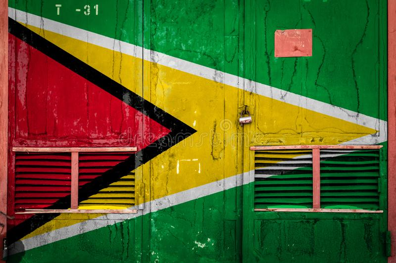 Close-up of old warehouse gate with national flag. Of Guyana. Concept of Guyana export-import, storage of goods and national delivery of goods. Flag in grunge royalty free illustration