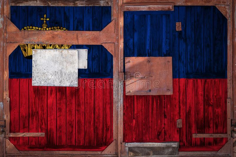 Close-up of old warehouse gate with national flag. Of Liechtenstein. The concept of export-import Liechtenstein, storage of goods and national delivery of goods royalty free illustration