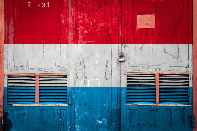 Close-up of old warehouse gate with national flag. Of Luxembourg. Concept of Luxembourg export-import, storage of goods and national delivery of goods. Flag in royalty free illustration
