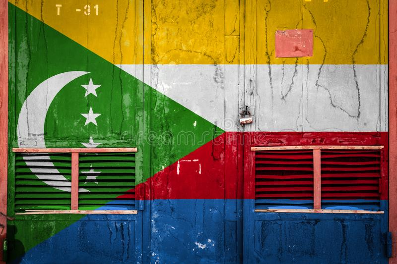 Close-up of old warehouse gate with national flag. Of Comoros. Concept of Comoros export-import, storage of goods and national delivery of goods. Flag in grunge stock illustration