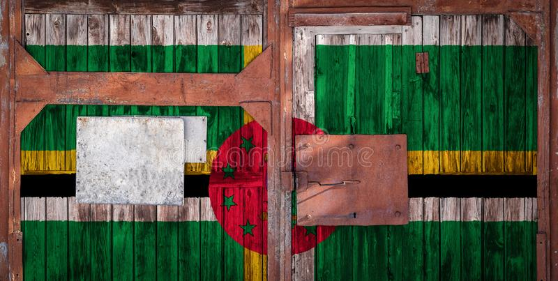 Close-up of old warehouse gate with national flag. Close-up of an old warehouse gate with the national flag of Dominica. The concept of export-import Dominica stock illustration