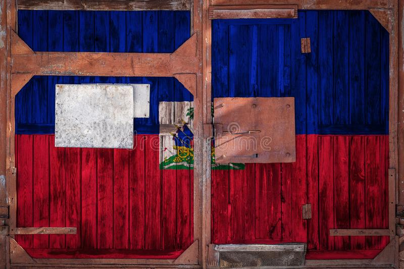 Close-up of old warehouse gate with national flag. Of Haiti. The concept of export-import of Haiti, storage of goods and national delivery of goods. Flag in royalty free illustration