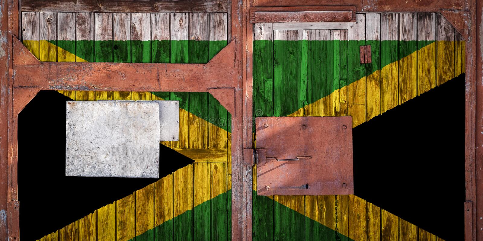 Close-up of old warehouse gate with national flag. Close-up of an old warehouse gate with the national flag of Jamaica. The concept of export-import Jamaica stock illustration