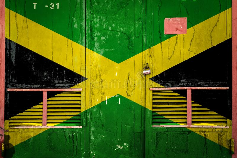 Close-up of old warehouse gate with national flag. Of Jamaica. Concept of Jamaica export-import, storage of goods and national delivery of goods. Flag in grunge stock illustration