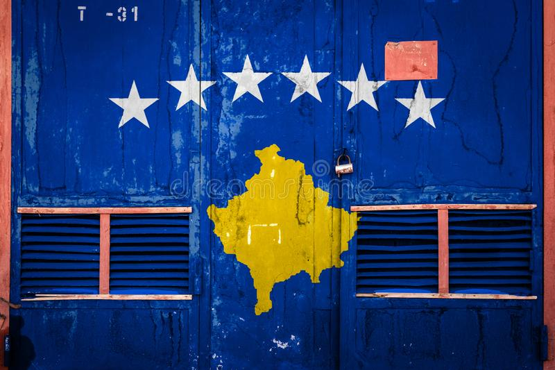 Close-up of old warehouse gate with national flag. Of Kosovo. Concept of Kosovo export-import, storage of goods and national delivery of goods. Flag in grunge royalty free illustration