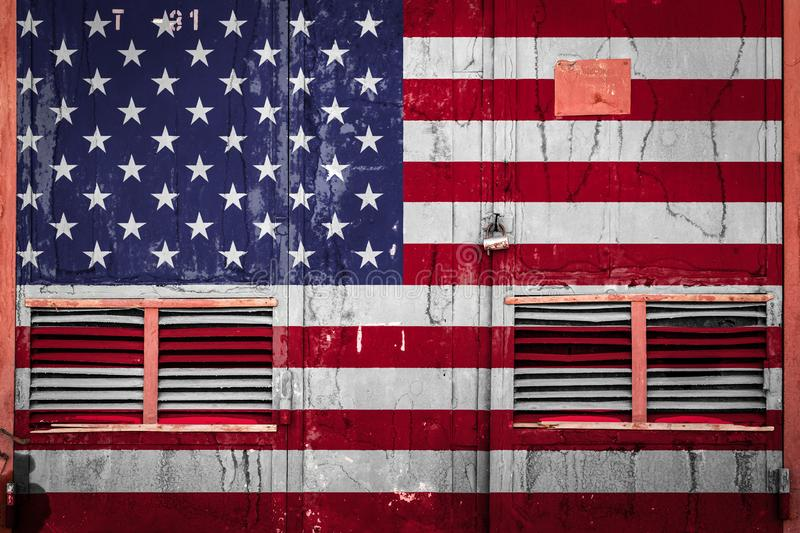 Close-up of old warehouse gate with national flag. Of USA. Concept of USA export-import, storage of goods and national delivery of goods. Flag in grunge style stock illustration