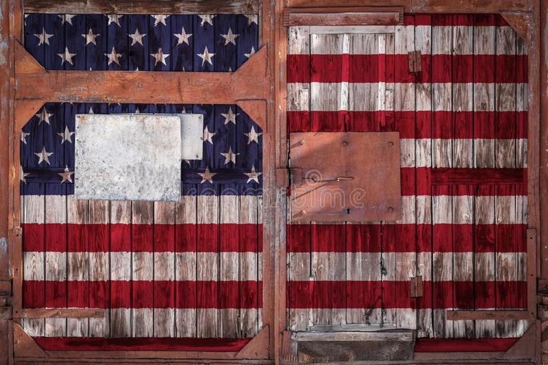 Close-up of old warehouse gate with national flag. Close-up of old warehouse gate with national usa flag. The concept of export-import USA, storage of goods and royalty free illustration