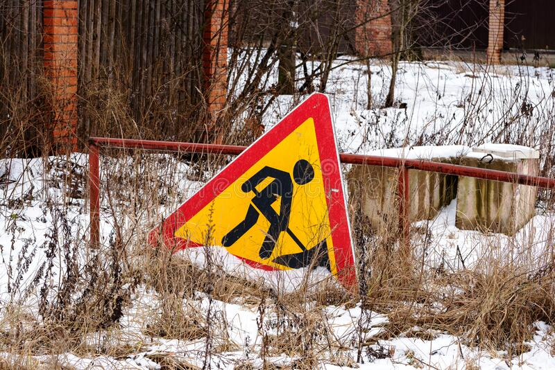 Close-up of an old warning sign on the ground. Road sign work is underway stock photos