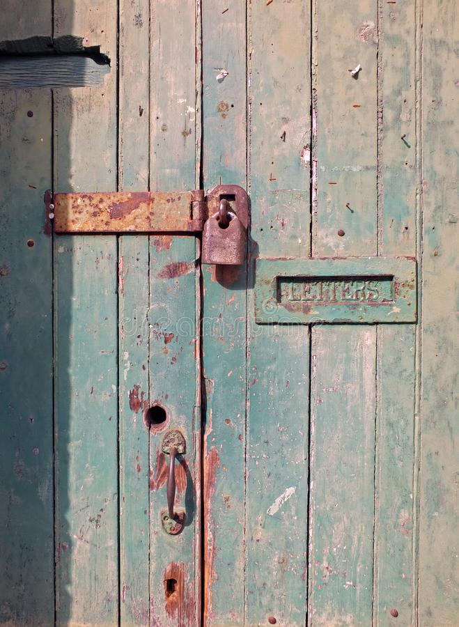 Close up of an old wooden door with green faded paint and a rusty closed padlock and old metal letterbox. Close up of an old wooden door with green faded paint royalty free stock photos