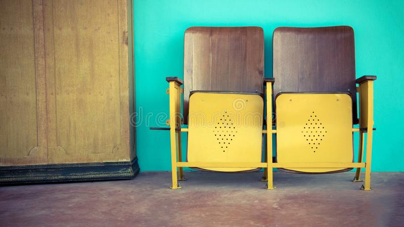 Close up of old wooden folding cinema chair or folding seat in front of Asian theater. stock photography
