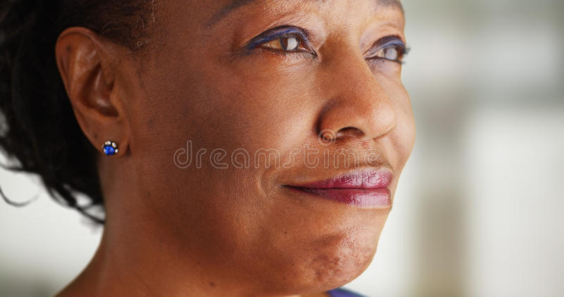 A close-up of an older black woman being very happy.  stock photos