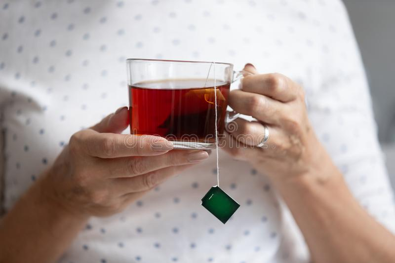Close up older mature woman holding cup of black tea royalty free stock images