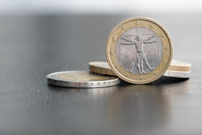 Close up of a one euro coin on blurred background showing the Vitruvian Man, a drawing by Leonardo da Vinci royalty free stock photography