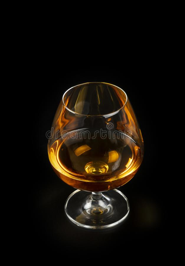 Glass of cognac or brandy isolated on black stock photography