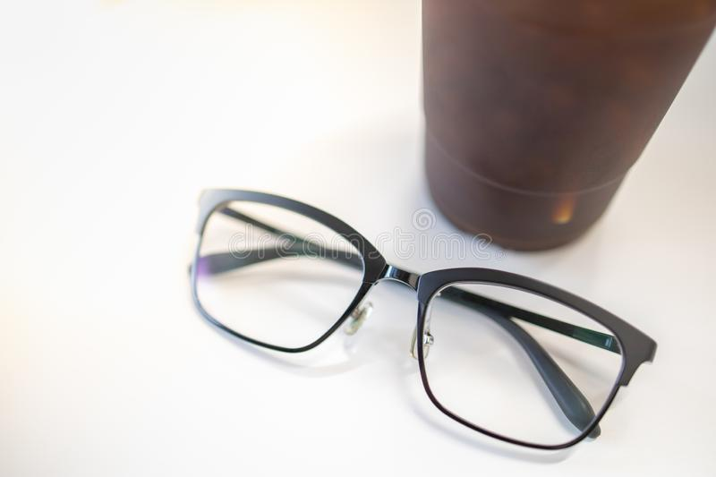 Close up oof readding glasses with plastic cup of iced black coffee on white table. Close up of reading glasses with take away plastic cup of iced black coffee royalty free stock photo