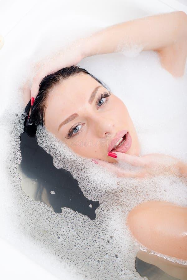 Close-up op aantrekkelijke mooie sexy jonge vrouw met blauwe ogen rode manicure die sensually het liggen in het bad van het kuuro royalty-vrije stock afbeeldingen
