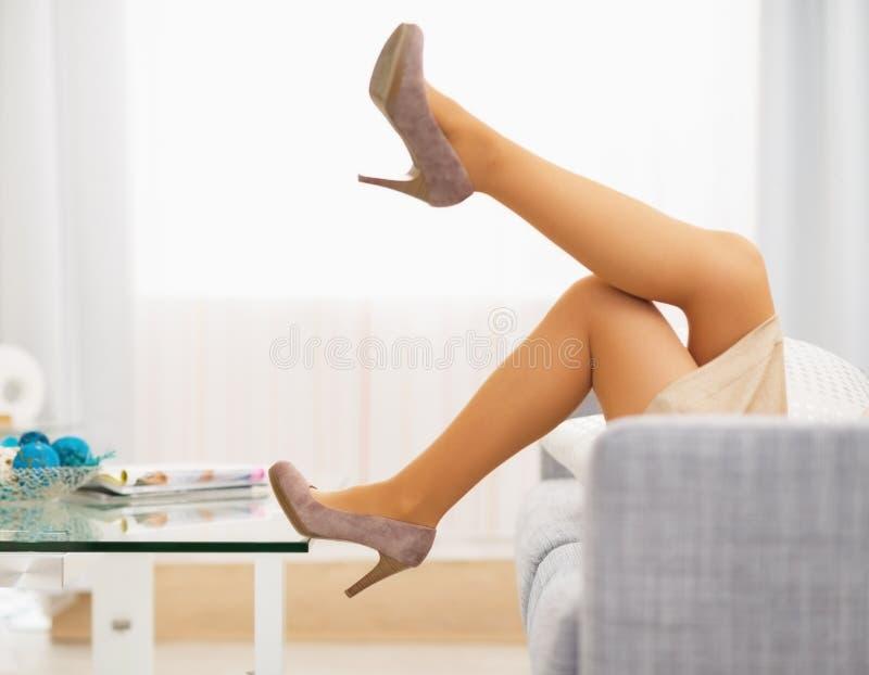 Close-up op been van het jonge huisvrouw leggen op divan stock afbeelding