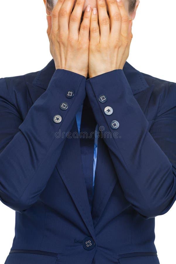 Close-up op beklemtoond bedrijfsvrouwen sluitend gezicht met handen stock afbeelding