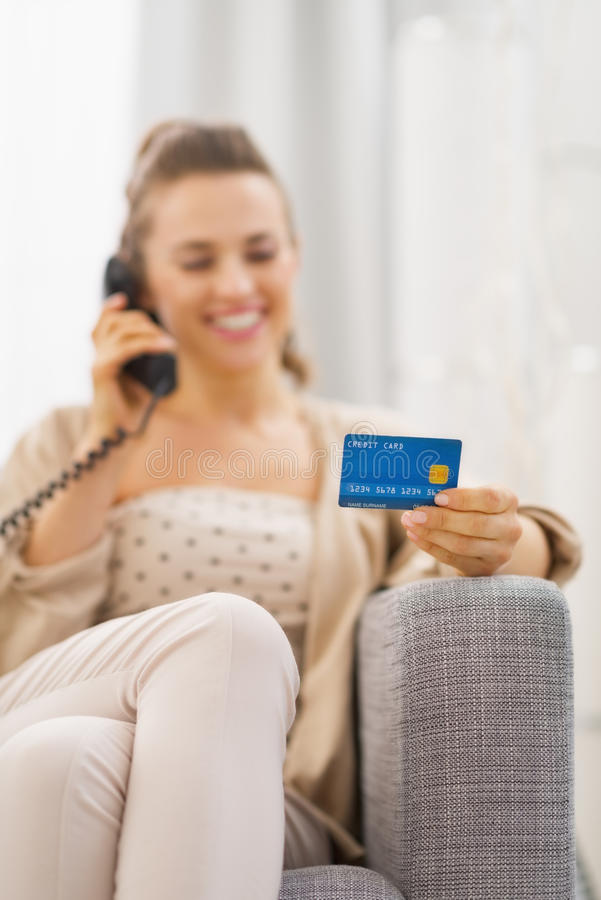 Close-up op creditcard ter beschikking van jonge vrouwen sprekende telefoon stock afbeeldingen