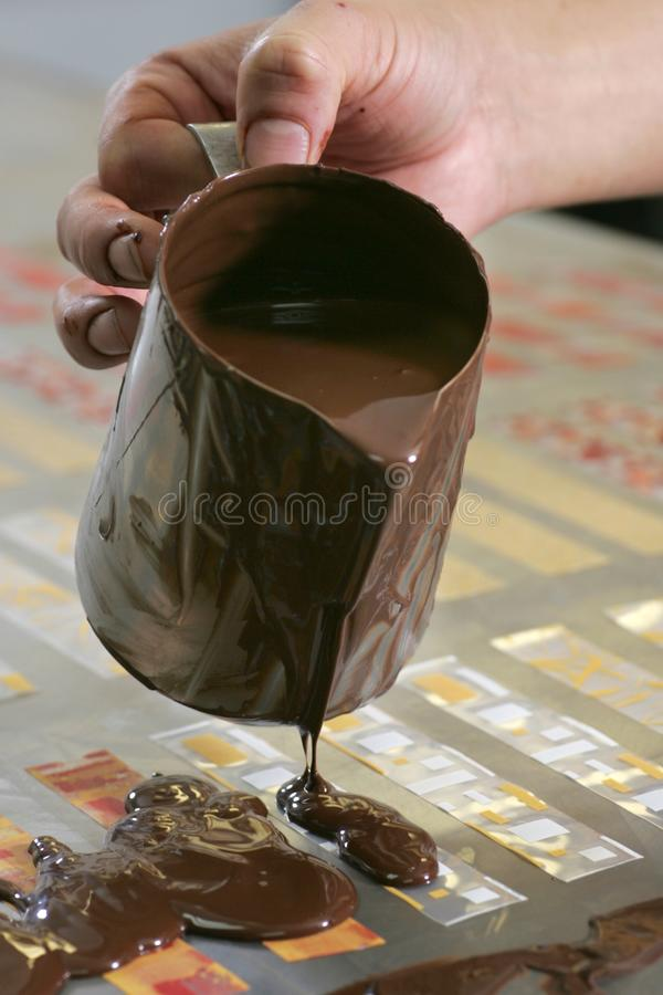 Close-up op de hand van een gebakjechef-kok Making Chocolate Cake royalty-vrije stock fotografie
