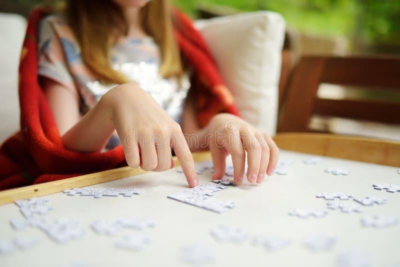 Close-up op de handen die van het kind een puzzel op een lijst assembleren stock foto