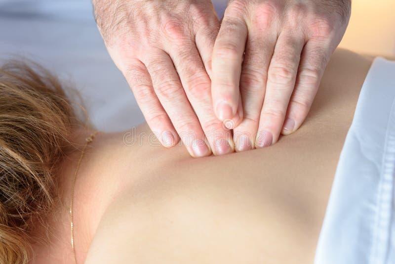 Close-up op de mens artsenhanden Kaukasische Vrouw die Therapeutische Achtermassage in medisch bureau ontvangen royalty-vrije stock foto's