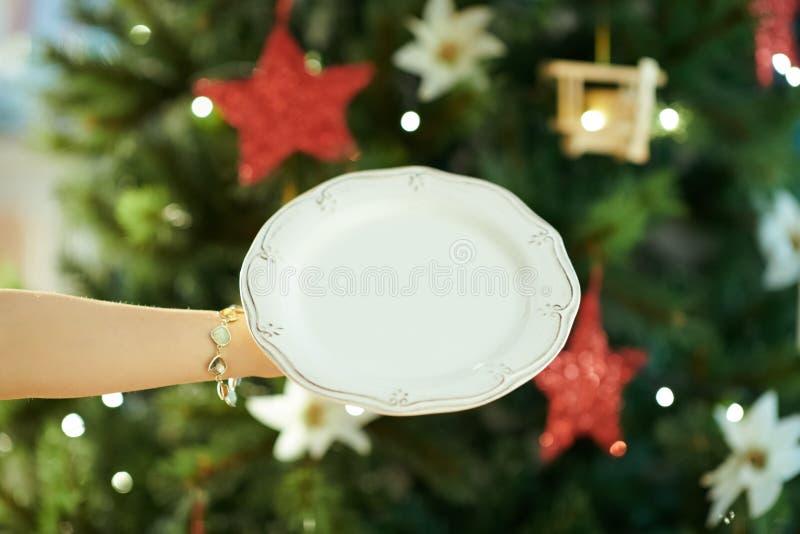 Close-up op dinerplaat ter beschikking van vrouw dichtbij Kerstboom royalty-vrije stock fotografie