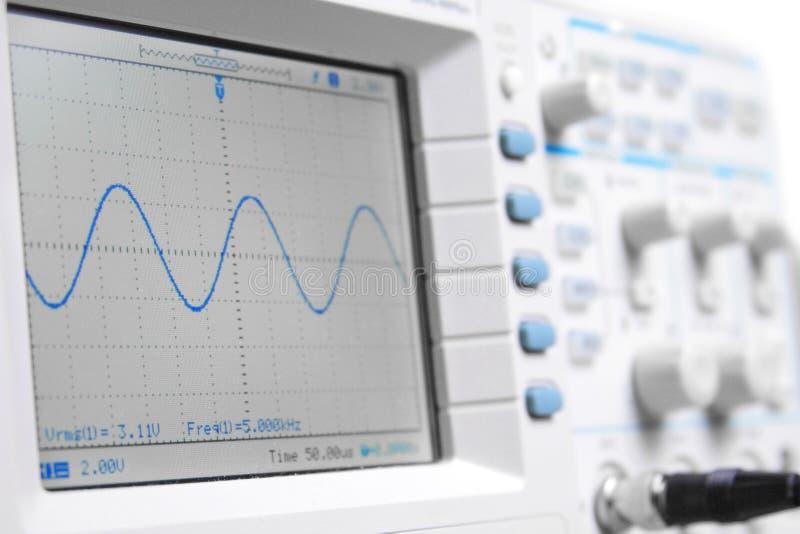 Close-up op een digitale oscilloscoop die een sinuso toont stock foto's