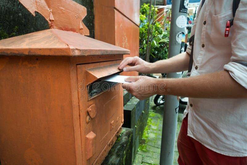 Close-up op een mannelijke hand die een brief in een gedenkwaardig vakje zetten Concept uitstekend type van mededeling royalty-vrije stock foto