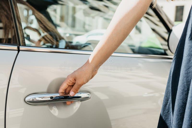 Close-up op een vrouwelijke hand die de deur van een nieuwe moderne auto openen stock afbeelding