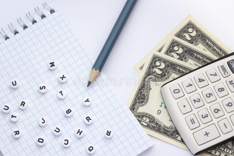 Close-up, op een witte calculator als achtergrond, geld en een blocnote met brieven stock foto