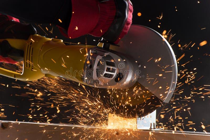 Close-up op elektrische zaag en handen van arbeider met vonken stock afbeelding