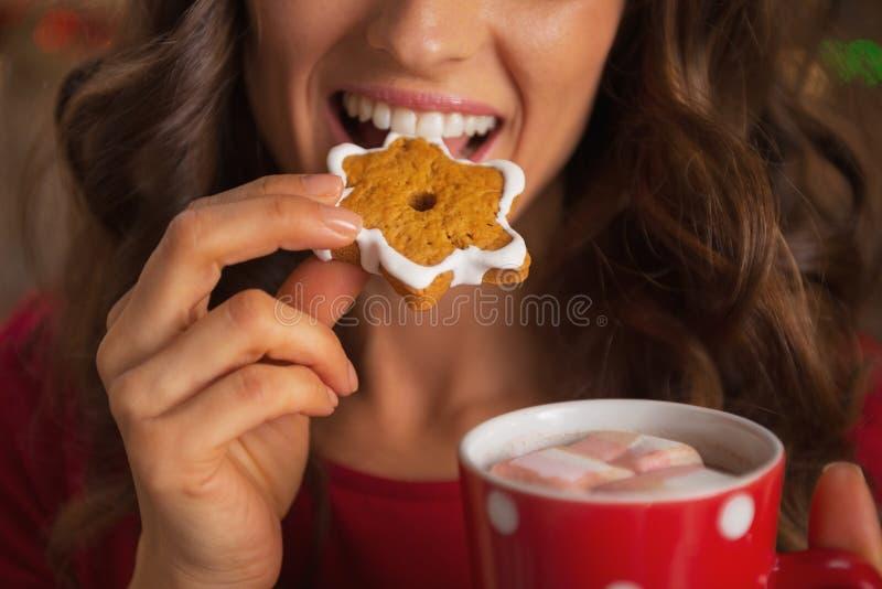 Close-up op gelukkige jonge vrouw die Kerstmiskoekje eten stock foto's