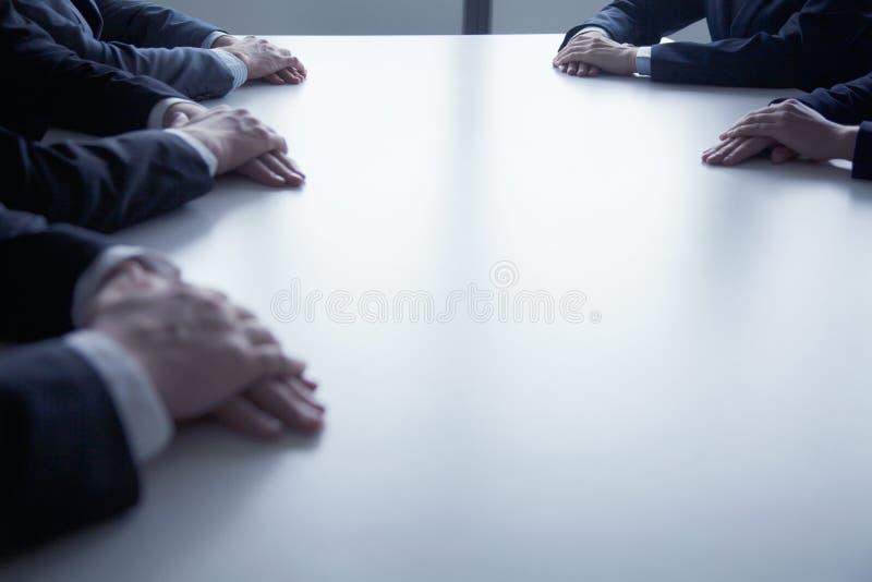Close-up op gevouwen handen van bedrijfsmensen bij de lijst tijdens een commerciële vergadering royalty-vrije stock foto