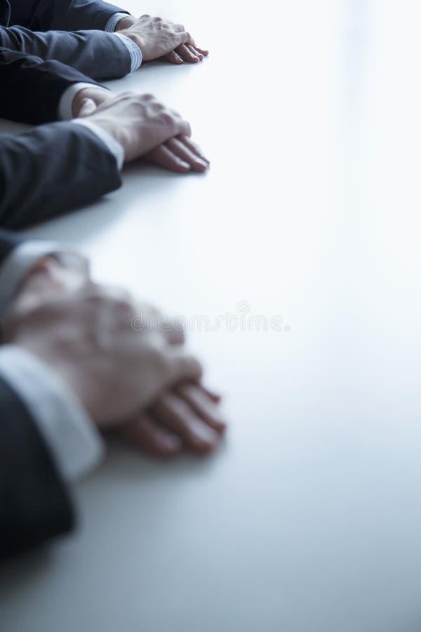 Close-up op gevouwen handen van bedrijfsmensen bij de lijst tijdens een commerciële vergadering stock foto