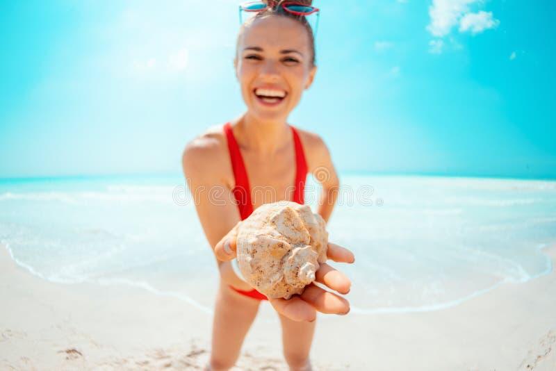 Close-up op glimlachende jonge vrouw op zeekust die overzeese shell tonen stock foto's