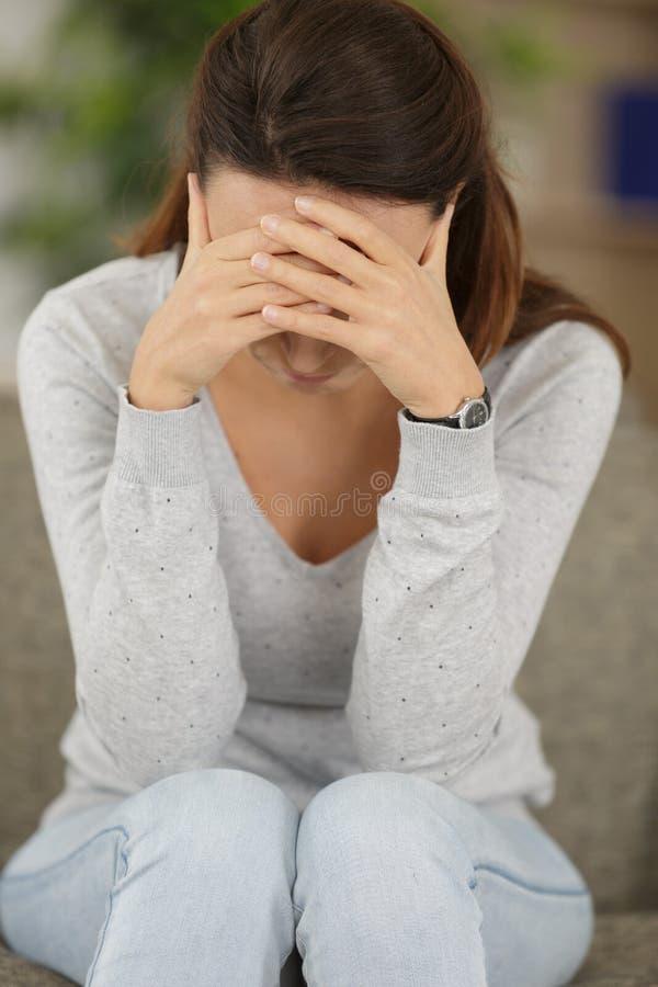 Close-up op hand gefrustreerde huisvrouwenzitting op laag stock fotografie