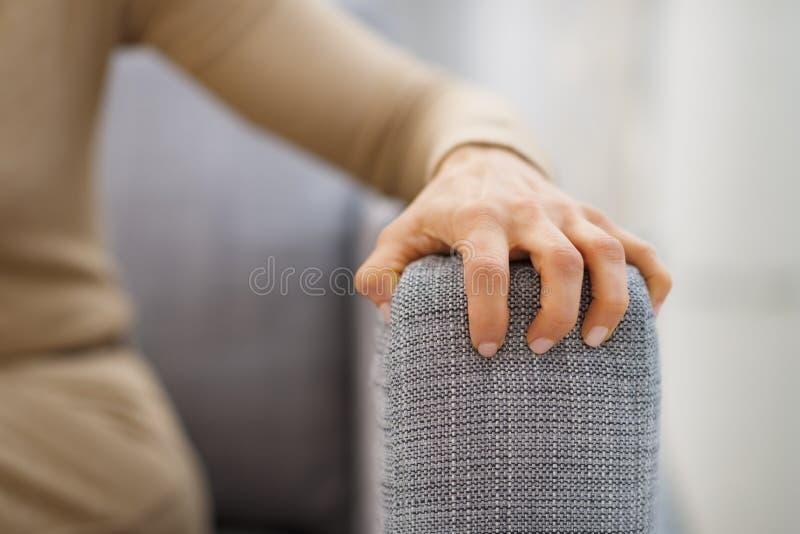 Close-up op hand van beklemtoonde vrouwenzitting op divan stock foto's
