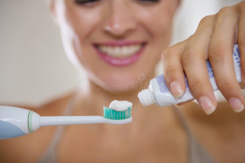 Close-up op handen die tandpasta bij de borstel drukken royalty-vrije stock foto's